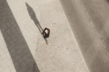 Young woman walking on pavement - MMFF000710