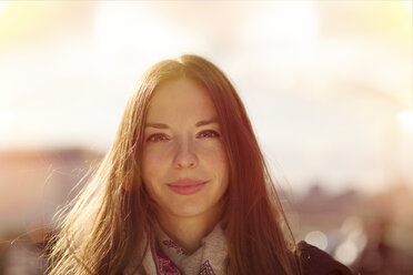 Portrait of smiling young woman at backlight - MMFF000712