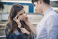 Young woman telephoning while boyfriend caressing her face - RAEF000152