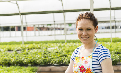 Young female gardener working in plant nursery - UUF003978