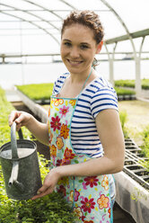 Young female gardener watering plants in nursery - UUF003983