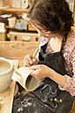 Potter in workshop working on earthenware jug - MAEF010371