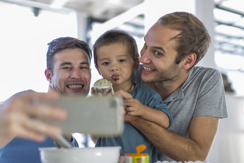 Gay couple baking cake with son - ZEF004470