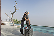 Gay couple with baggage hugging on a terrace at the poolside - ZEF004297
