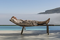 Man in bathrobe lying on a lounge next to pool - ZEF004307