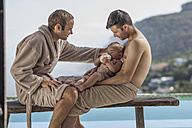 Gay couple bottle-feeding baby at the poolside - ZEF004338