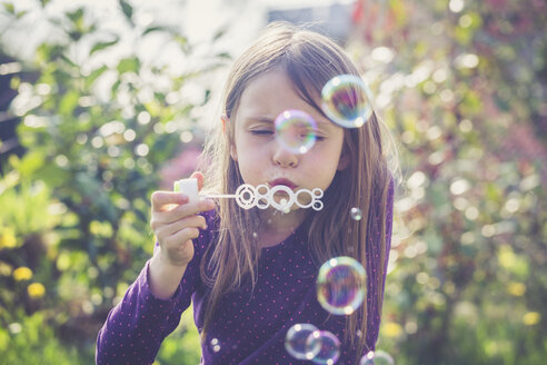 Girl blowing soap bubbles in a garden - SARF001753