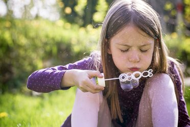 Girl blowing soap bubbles in a garden - SARF001755