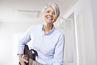 Mature woman playing electric guitar - FMKF001444