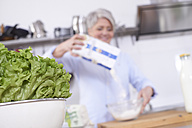 Lettuce and mature woman in kitchen pouring flour in bowl - FMKF001446
