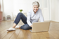 Mature woman sitting on floor using laptop - FMKF001454
