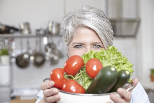 Mature woman holding pot with vegetables - FMKF001463