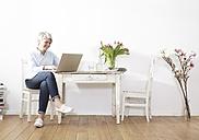 Mature woman sitting at table using laptop - FMKF001472