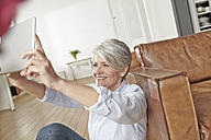 Mature woman at home taking selfie with digital tablet - FMKF001487
