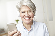 Mature woman holding smartphone and wearing headphones - FMKF001489