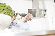 Mature woman baking in kitchen - FMKF001493