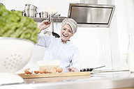 Mature woman baking in kitchen - FMKF001497