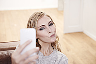 Young woman pouting mouth taking selfie - FMKF001506