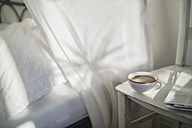Cup of coffee and newspaper on an old chair at bedroom - RIBF000052