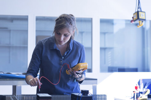 Technician in workshop checking electrical device - SGF001565