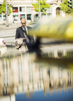 Businessman in the city looking on smartphone - UUF004023