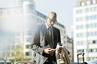 Businessman in the city looking on smartphone - UUF004009