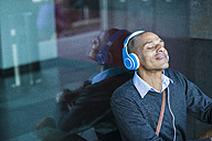 Man wearing headphones leaning against glass front - UUF004021
