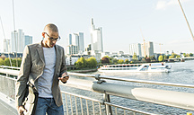 Germany, Frankfurt, businessman on bridge looking on smartphone - UUF004037