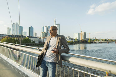 Germany, Frankfurt, businessman on bridge with briefcase and smartphone - UUF004077