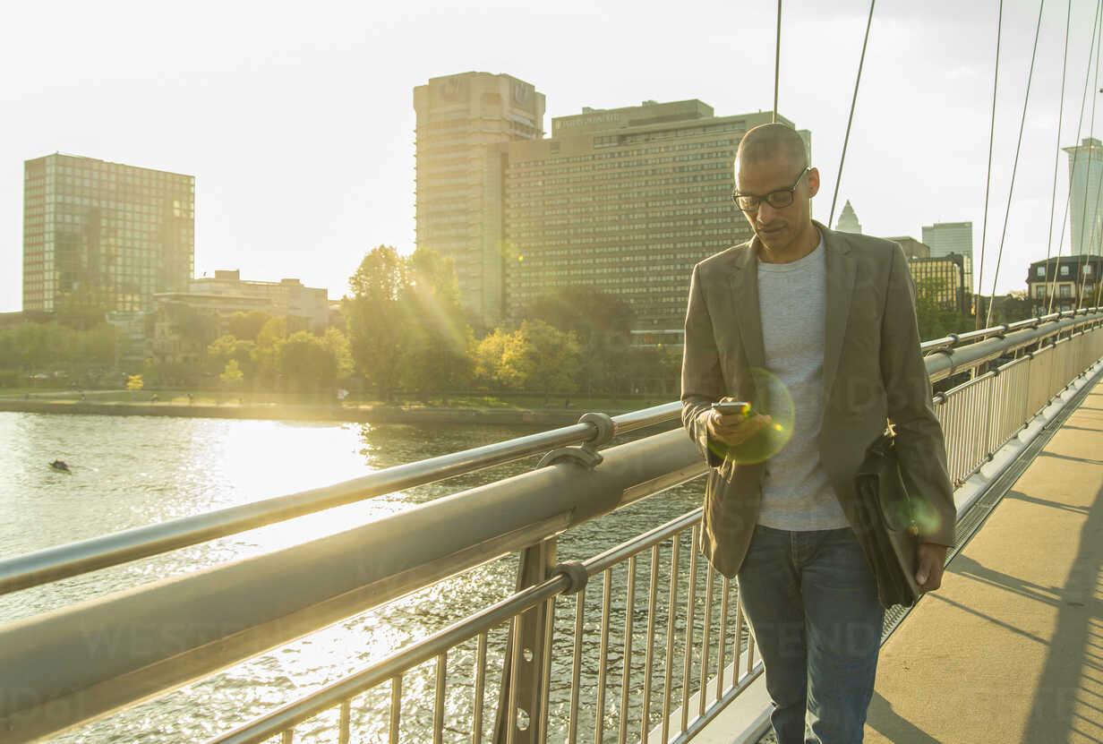 Germany, Frankfurt, businessman on bridge looking on smartphone - UUF004041 - Uwe Umstätter/Westend61