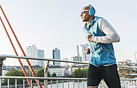 Germany, Frankfurt, man wearing headphones jogging on bridge - UUF004078