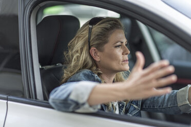 Frustrated woman in car stuck in traffic jam - ZEF004898