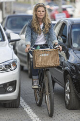 Woman on bicycle in traffic jam - ZEF004611