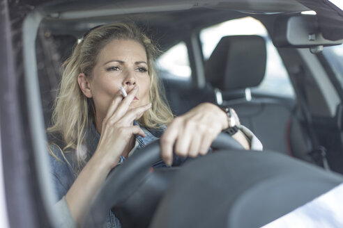 Serious woman in car smoking a cigarette - ZEF004680