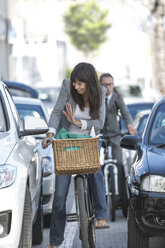 Woman on bicycle waving at car - ZEF004682
