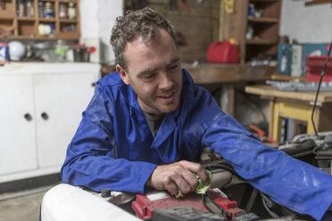 Man working on car in home garage - ZEF004814
