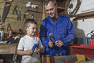 Father and son working in home garage - ZEF004820