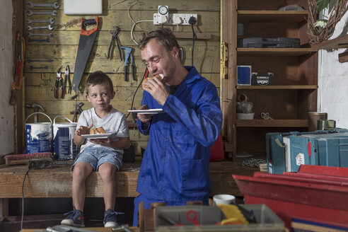 Father and son working in home garage having lunch break - ZEF004822