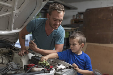 Son helping father in home garage working on car - ZEF004826