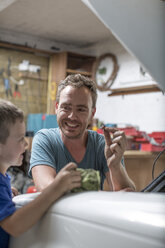Son helping father in home garage working on car - ZEF004828