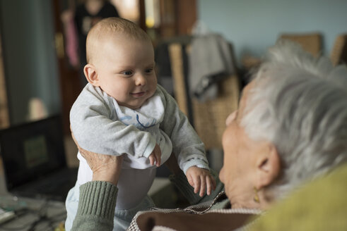 Baby boy smiling to an elderly woman at home - RAEF000163