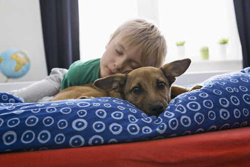 Boy and dog lying on bed - PDF000916