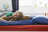 Boy and dog lying on bed - PDF000919
