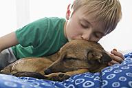 Boy and dog cuddling on bed - PDF000921