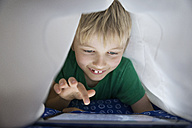 Boy using digital tablet in bed under blanket - PDF000931