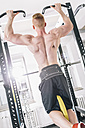 Young man exercising chin-ups on power rack in gym - MADF000221