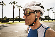 Spain, Mallorca, Sa Coma, portrait of triathlet with cycling helmet - MFF001607