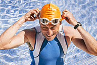 Spain, Mallorca, Sa Coma, smiling triathlet swimmer standing in a pool - MFF001613