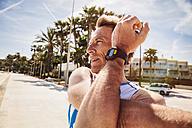 Spain, Mallorca, Sa Coma, triathlet stretching on the beach promenade - MFF001619