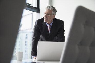 Businessman in conference room preparing for presentation - RBF002659